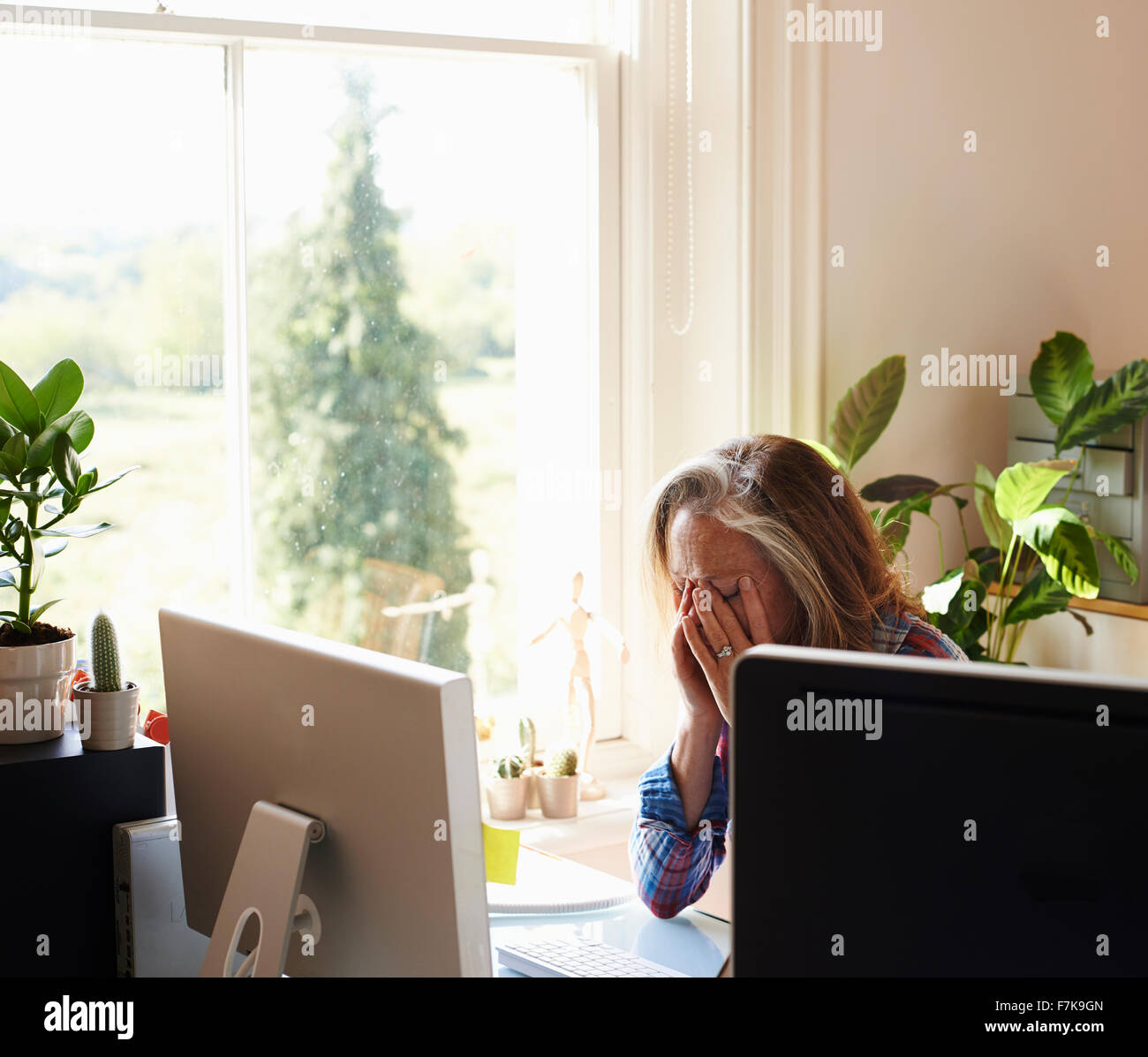 Tired woman with head in hands at computer in home office - Stock Image