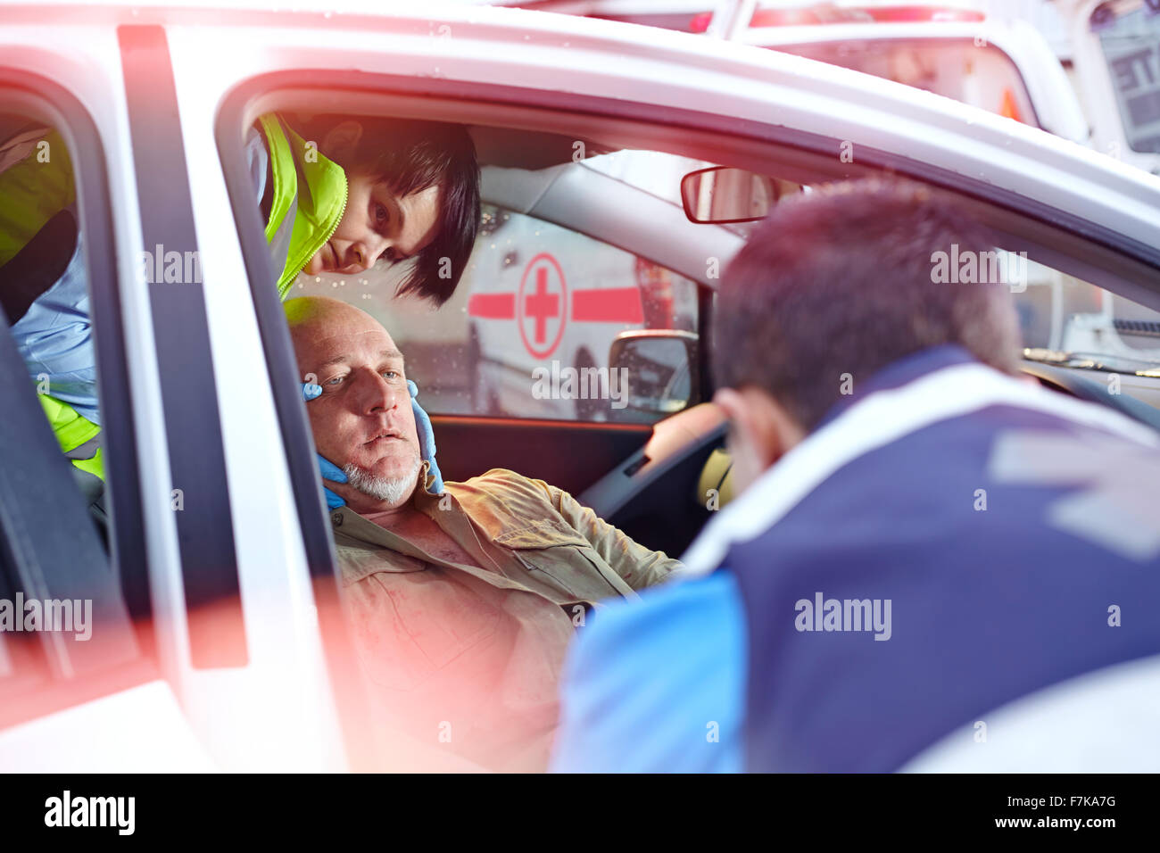 Rescue workers tending to car accident victim in car - Stock Image