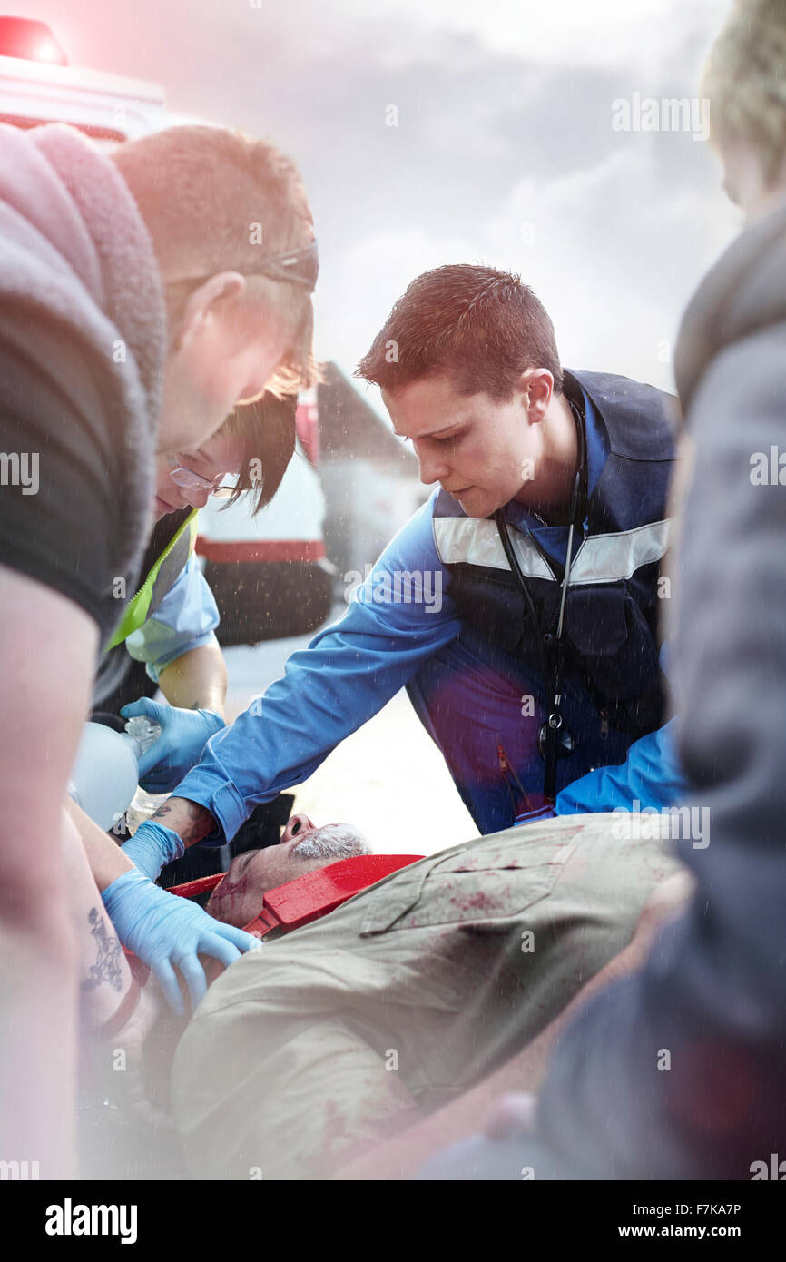 Rescue workers tending to car accident victim in road - Stock Image