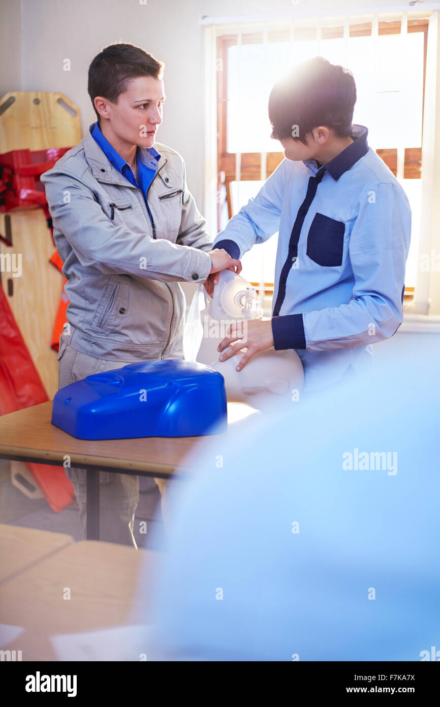 Instructor guiding student with manual resuscitator in CPR training class - Stock Image
