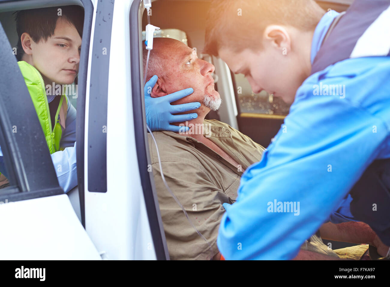 Rescue workers carefully tending to car accident victim in car - Stock Image