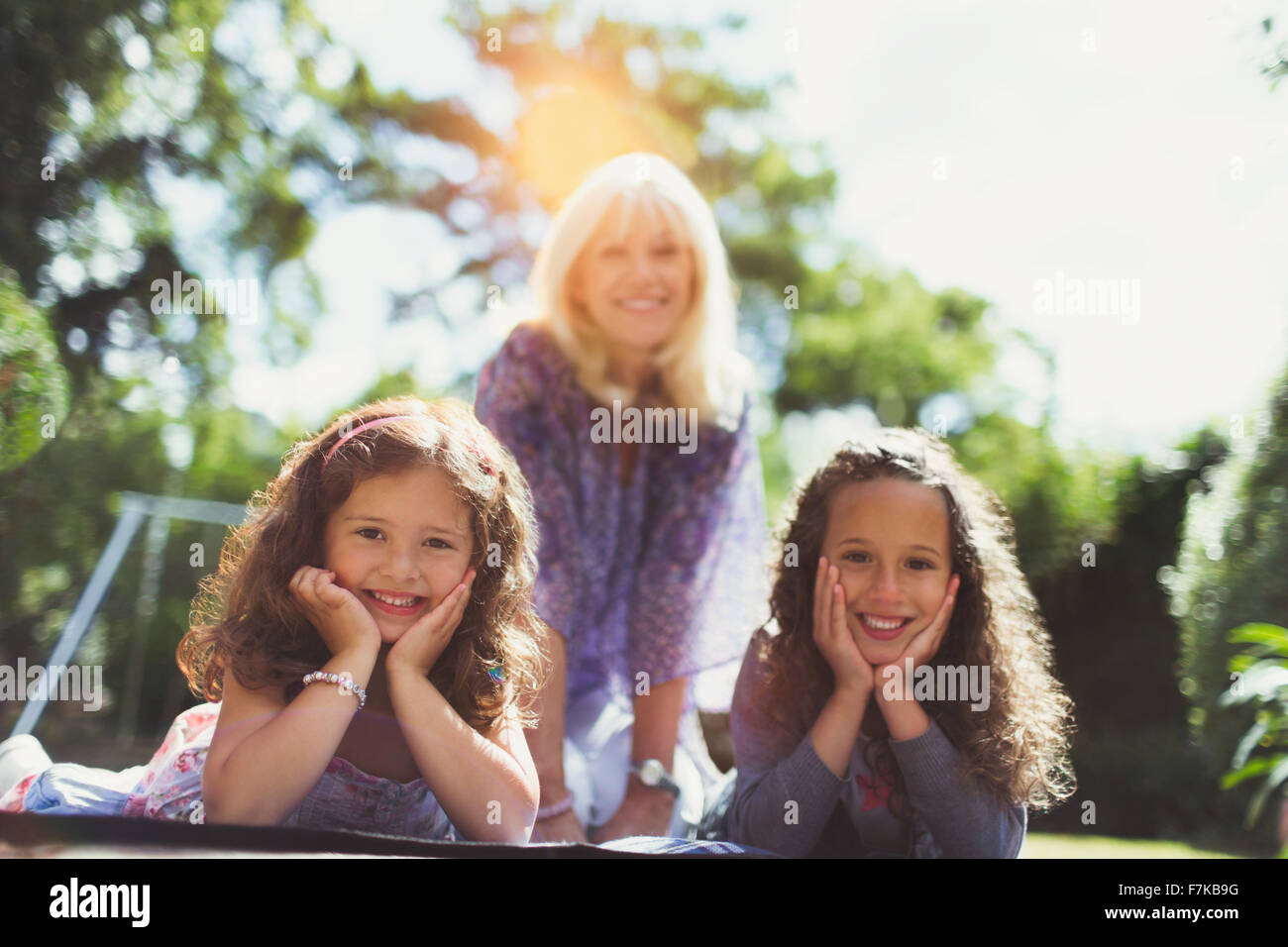 Portrait smiling grandmother with twin granddaughters in park - Stock Image