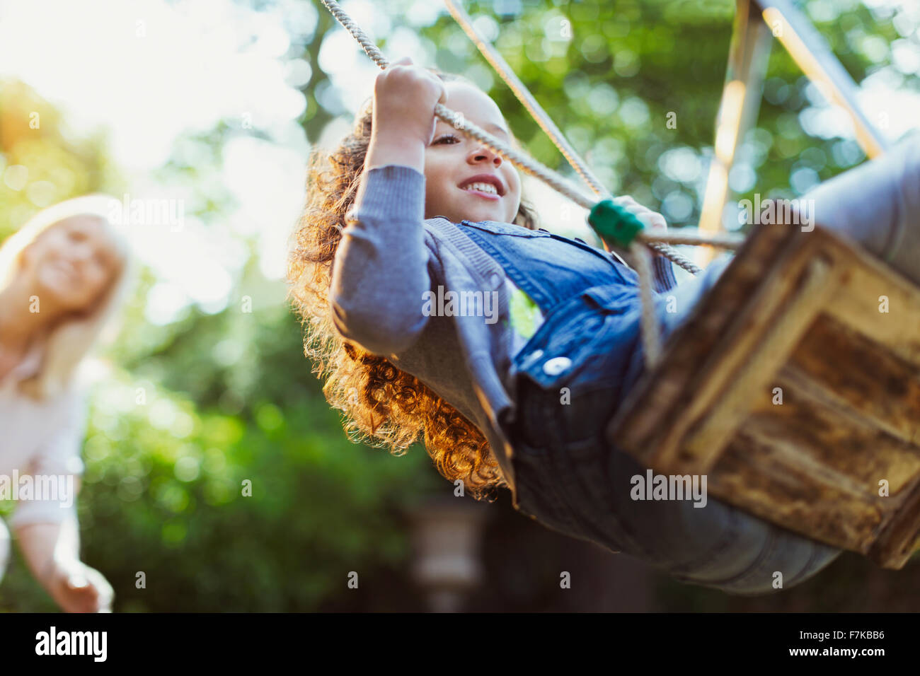 Carefree girl swinging in park - Stock Image