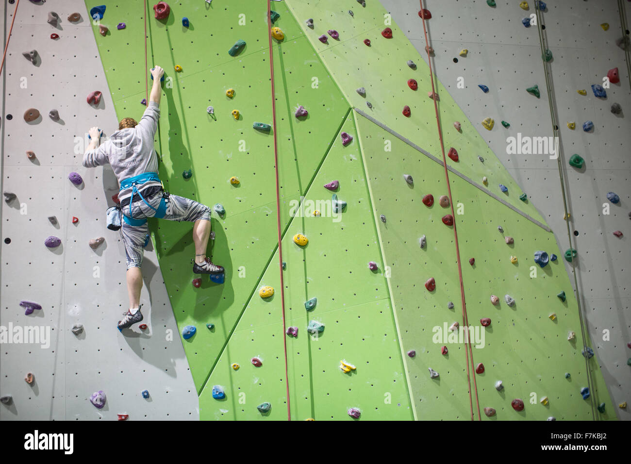 A female climber using an indoor climbing gym. - Stock Image
