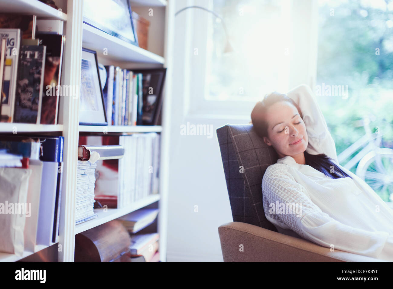 Serene woman napping in armchair - Stock Image