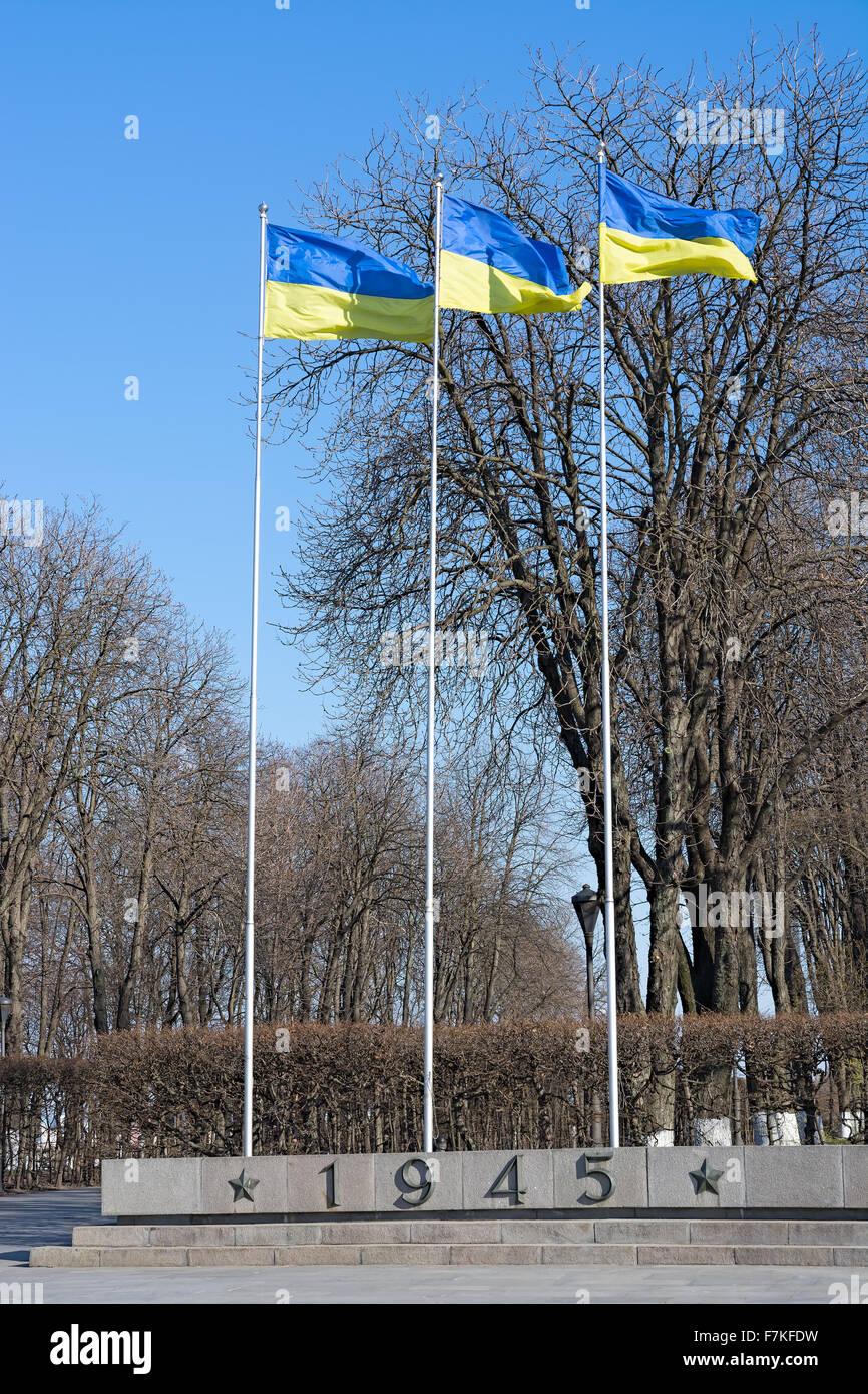 Three Ukrainian flag on flagpoles against the bright spring sky. Stock Photo