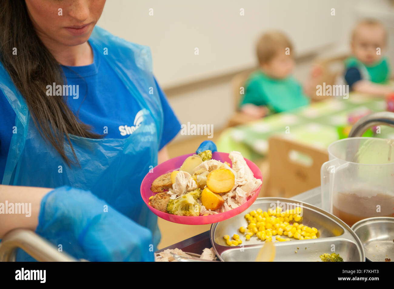 A nursery worker preparing a meal for children - Stock Image