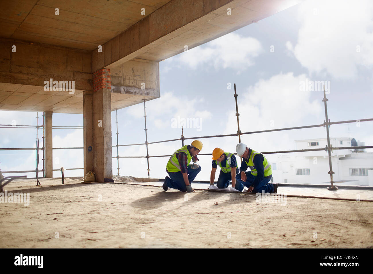 Construction workers working at highrise construction site - Stock Image