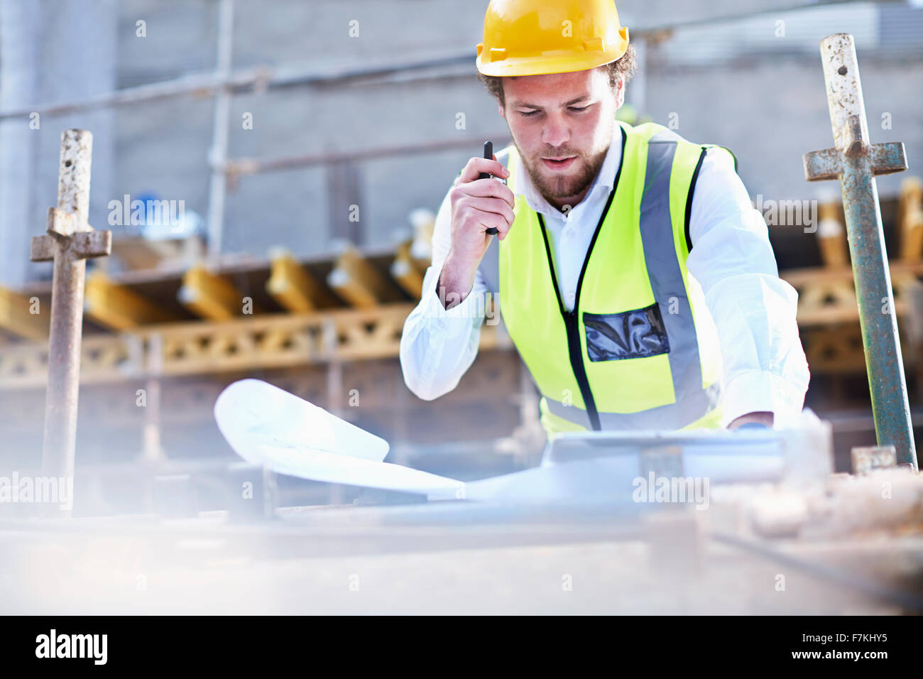 Engineer with blueprints and walkie-talkie working at construction site - Stock Image