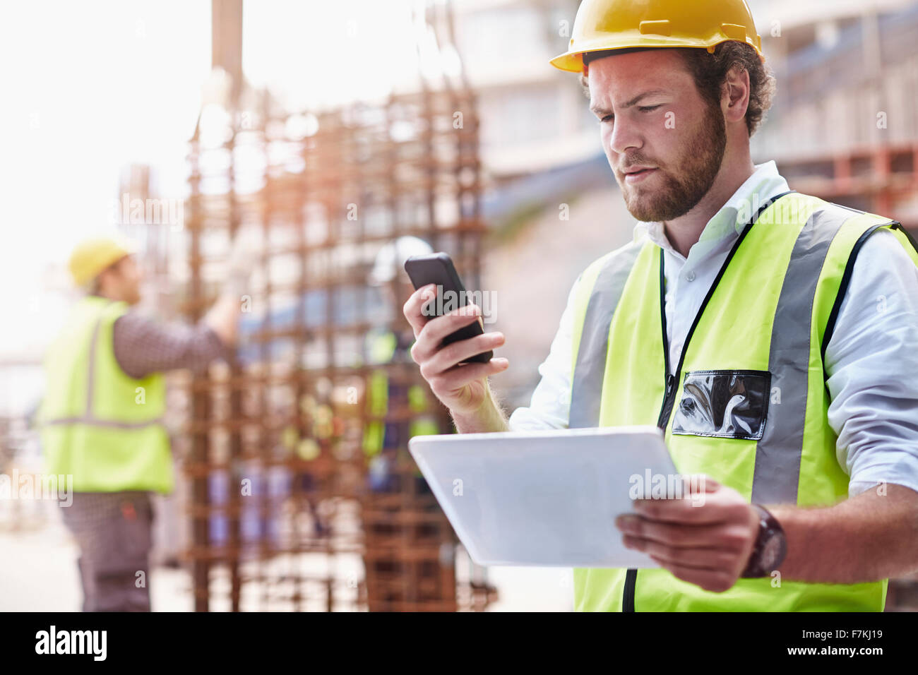 Construction worker with digital tablet texting with cell phone at construction site - Stock Image