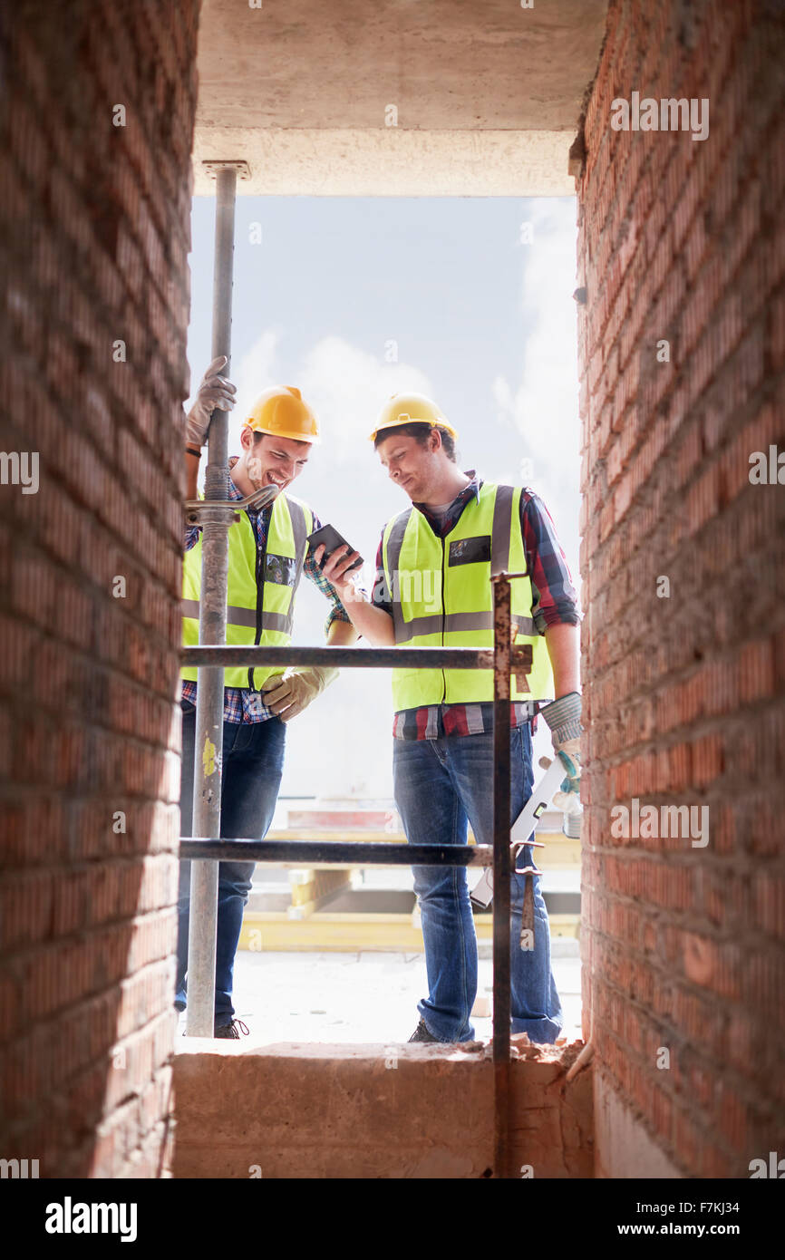 Construction workers texting with cell phone at construction site - Stock Image