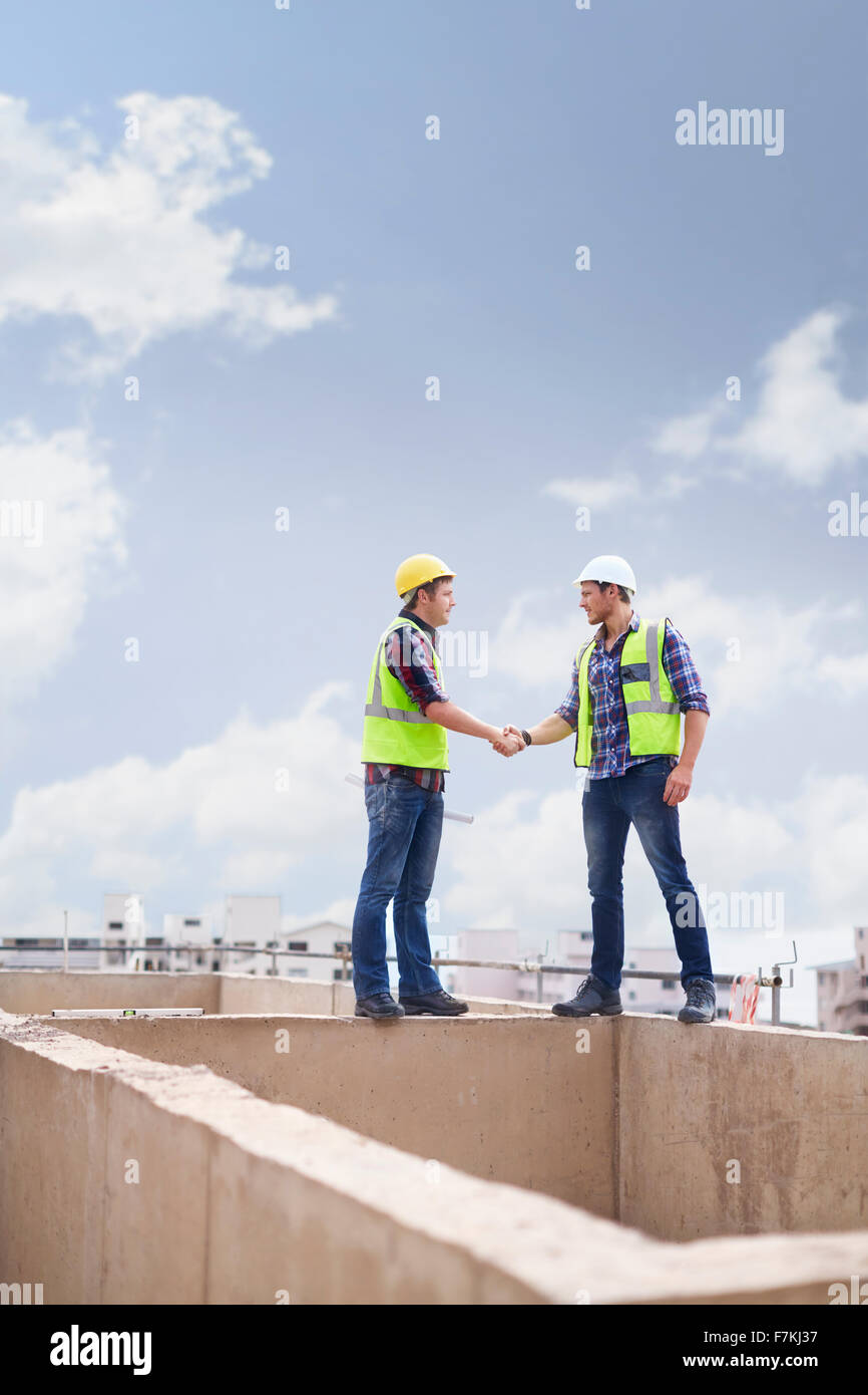 Construction workers handshaking at highrise construction site - Stock Image