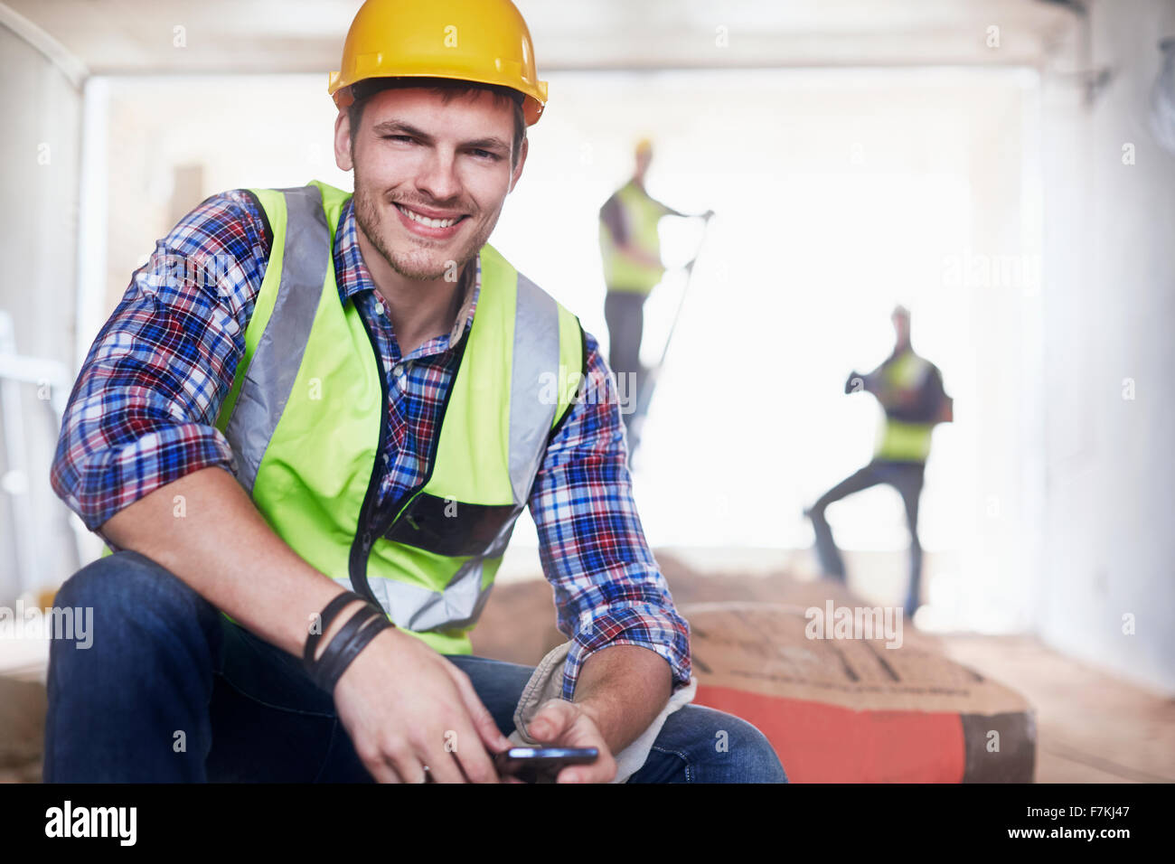 Portrait smiling construction worker with cell phone at construction site - Stock Image