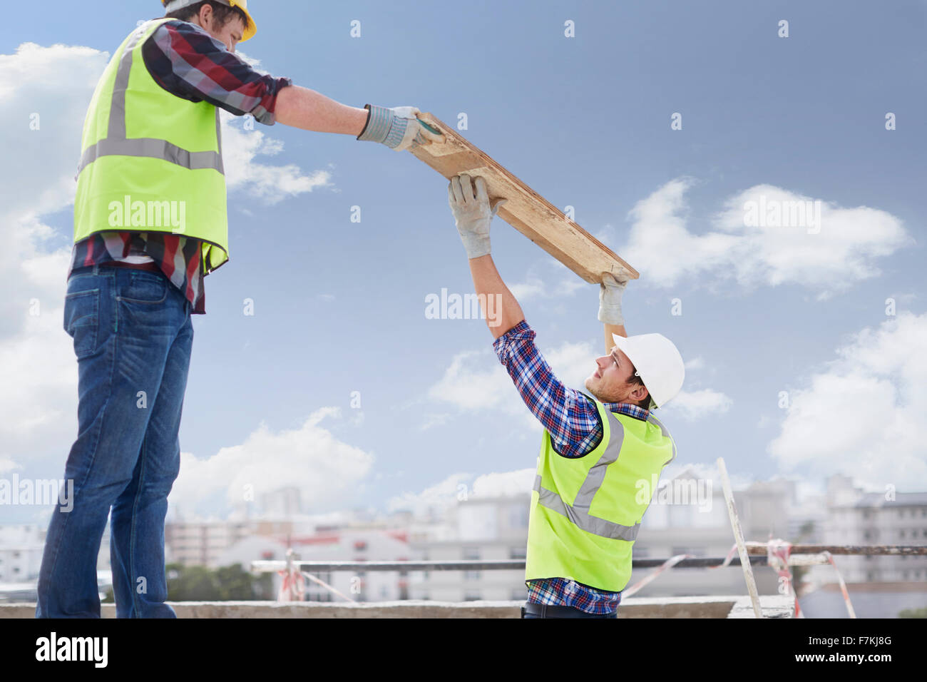 Construction workers lifting part at highrise construction site - Stock Image