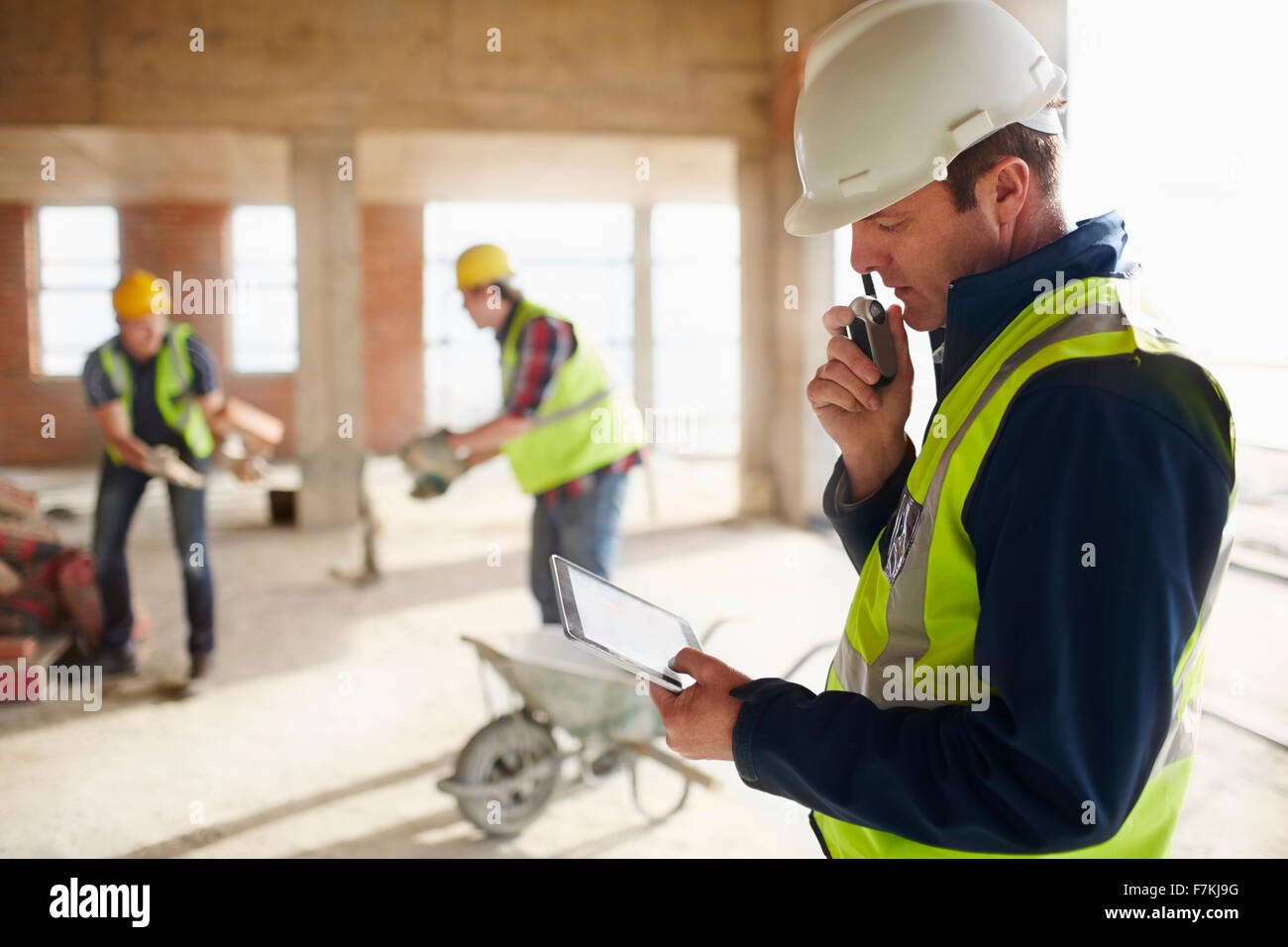 Foreman with digital tablet using walkie-talkie at construction site - Stock Image