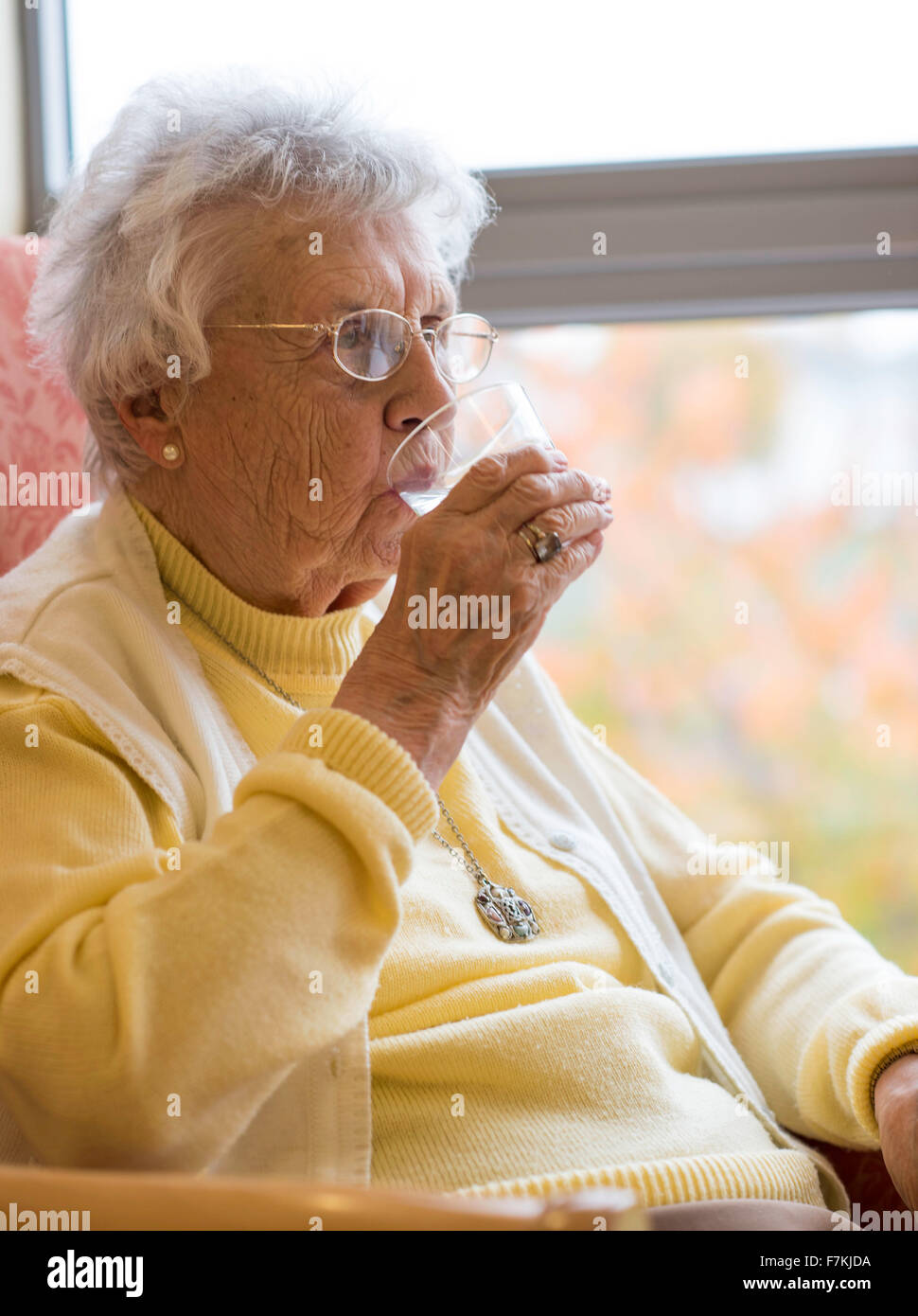 An old lady having a glass of water in an old folks home. - Stock Image