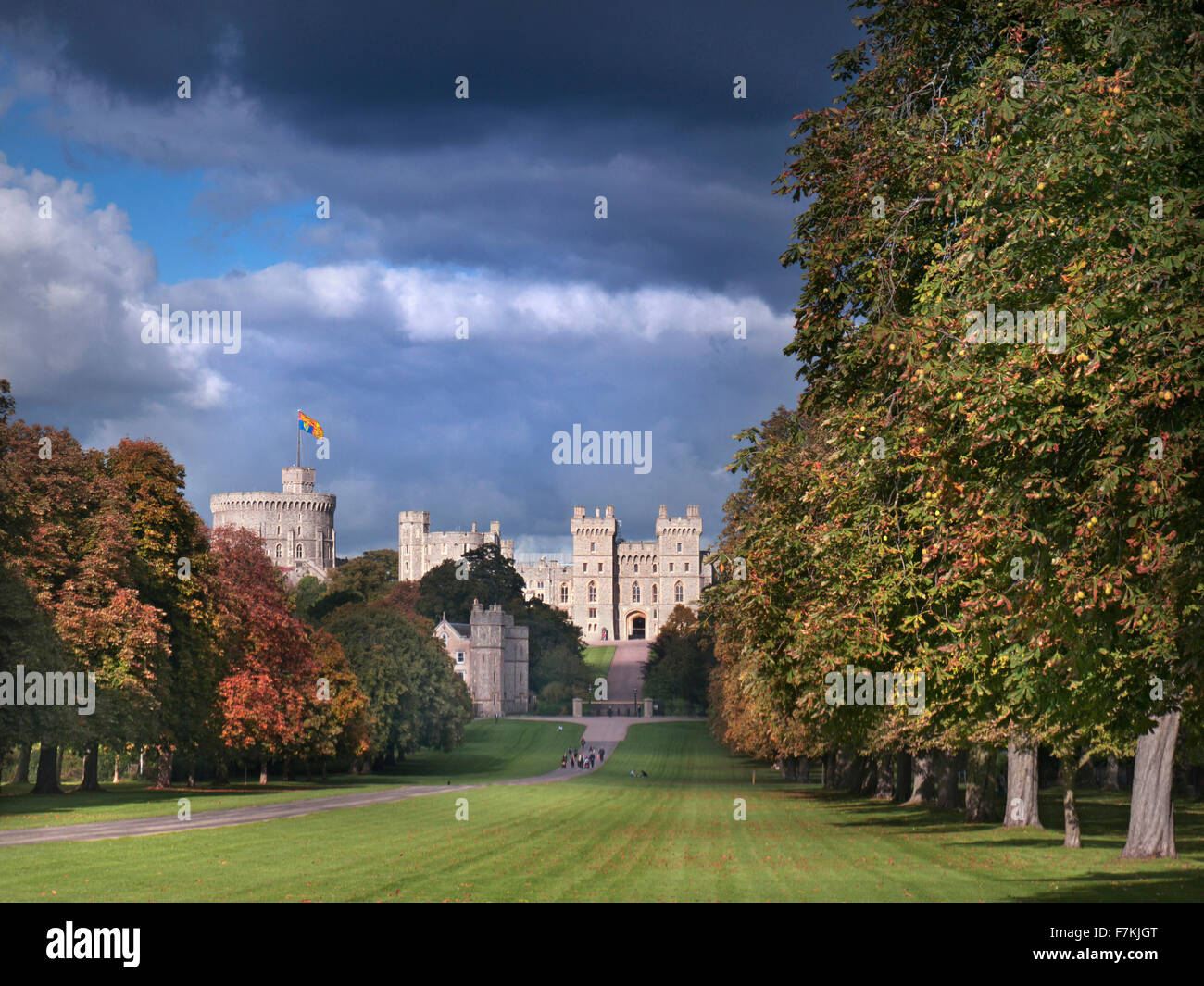 Windsor Castle flying Royal Standard viewed down the Long Walk with walkers, in autumnal colour with dramatic shafts - Stock Image