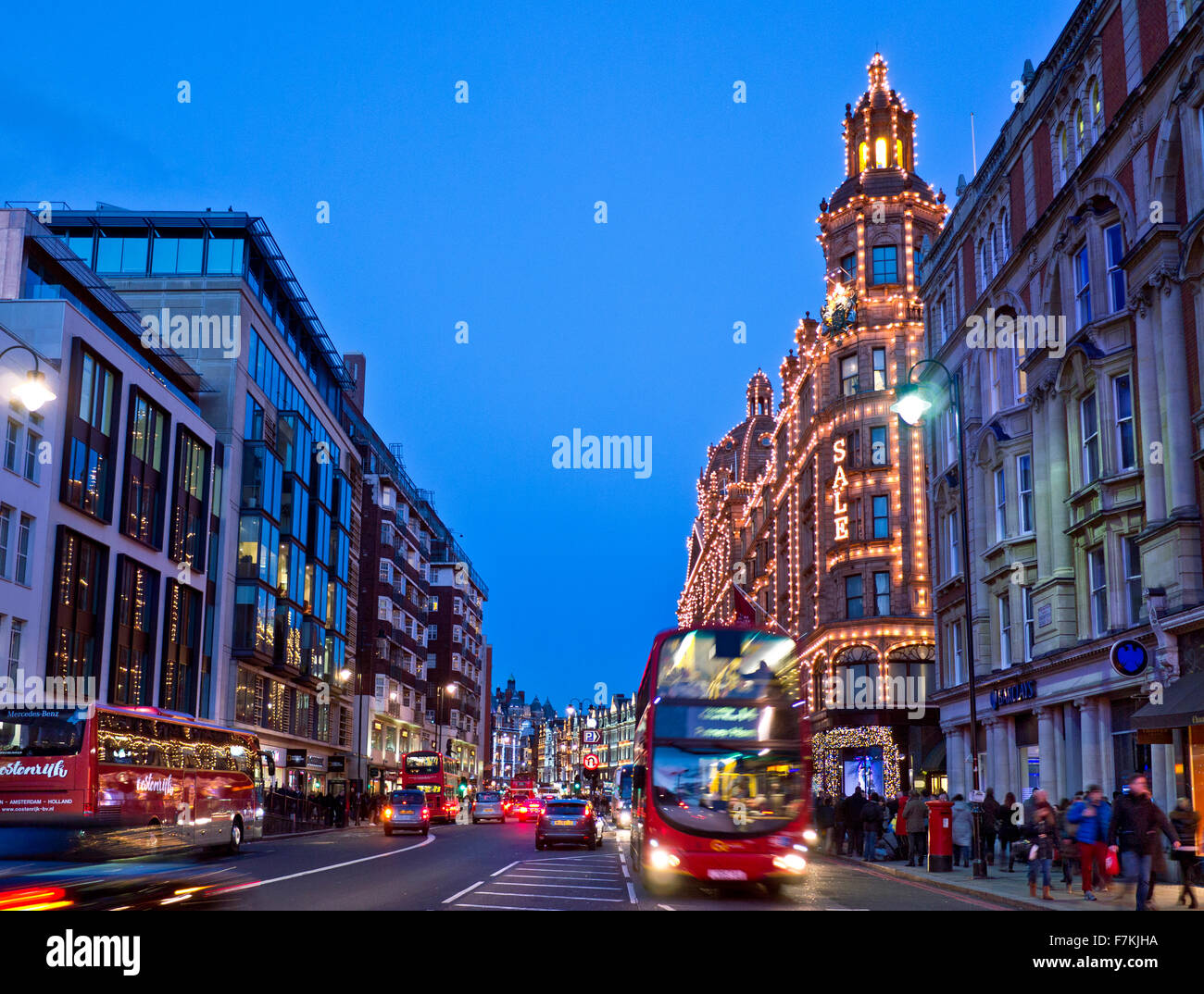 Brompton Road shops including Harrods store at dusk with lit 'Sale' sign shoppers red buses and taxis Knightsbridge - Stock Image