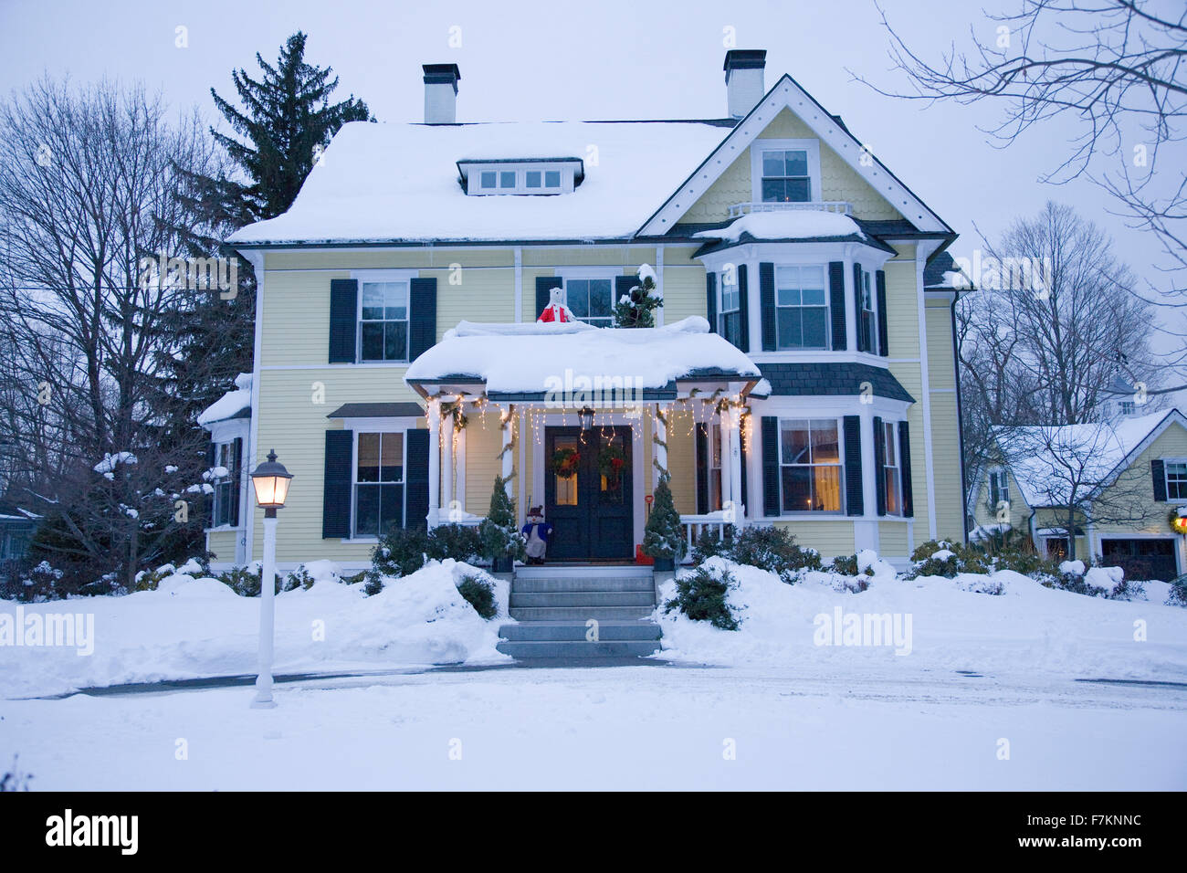 House with Christmas lights on in snow at dusk, Stow, MA ...