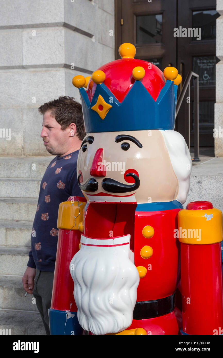 Washington, DC - A man smoking a cigarette stands next to a giant nutcracker at the Downtown Holiday Market. - Stock Image