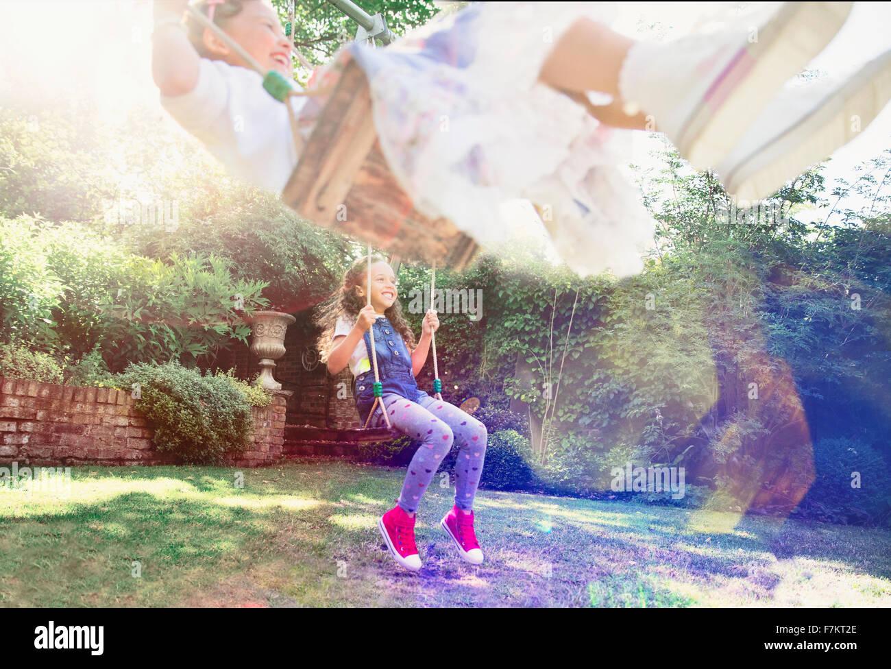 Girls swinging in backyard - Stock Image