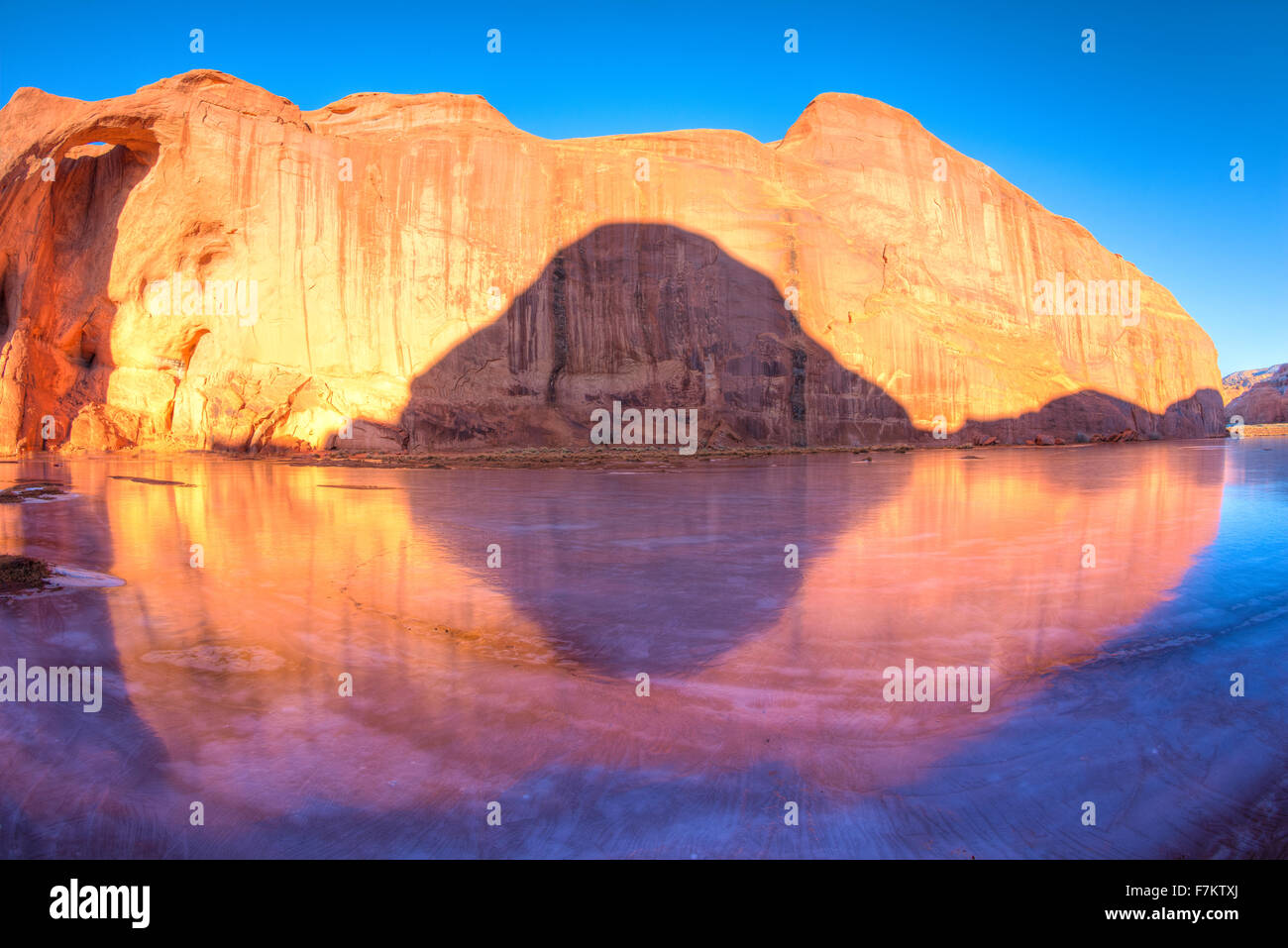 Eye of the Sun Arch reflected in ice, Monument Valley Tribal Park, Arizona   Navajo Reservation - Stock Image