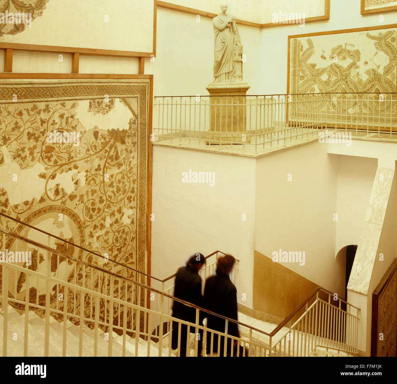 Two Tunisian women walk down a stairwell by a mosaic and statue display at the Bardo Museum in Tunis. The Bardo, Stock Photo