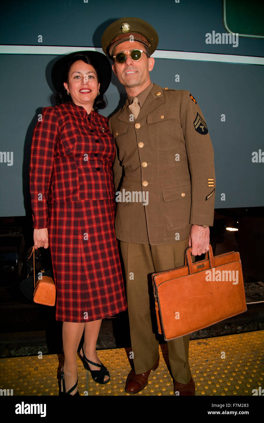 1940's Serviceman and wife pose in front of Pearl Harbor Day Troop train reenactment from Los Angeles Union - Stock Image