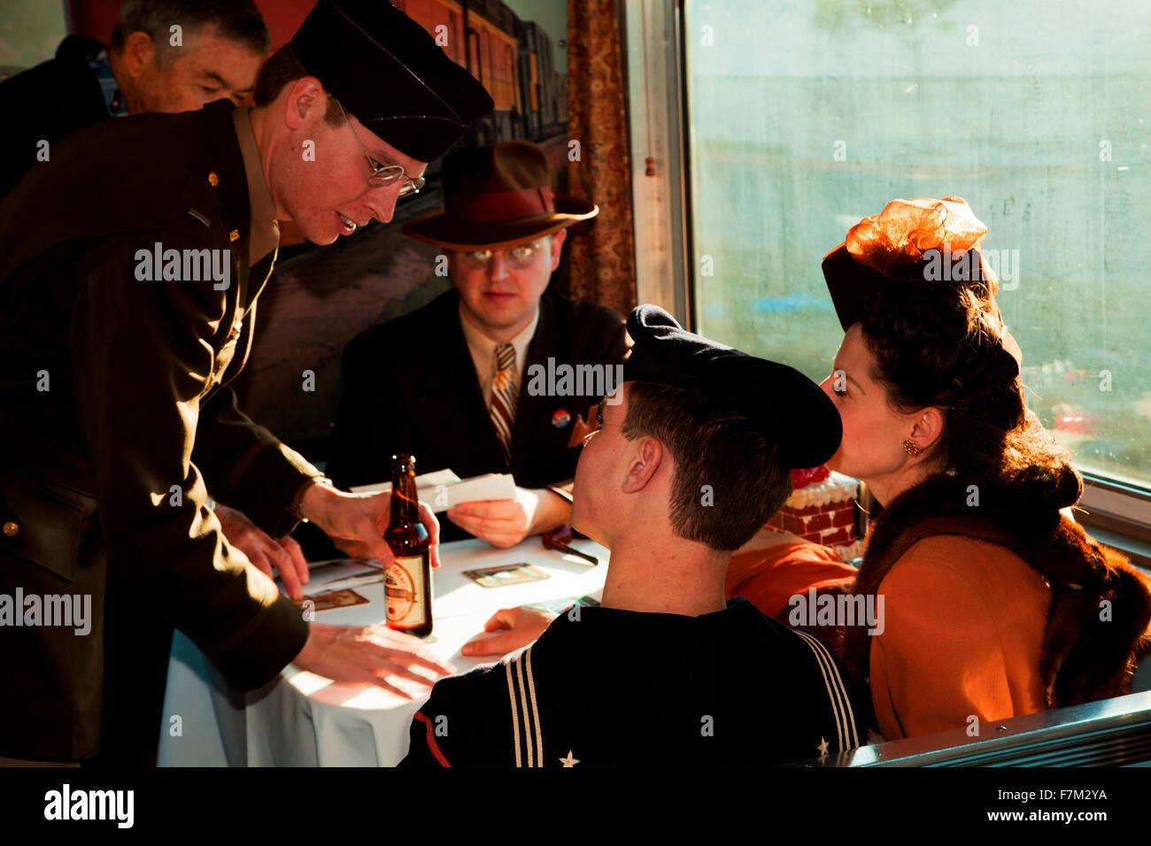 1940's reenactors look outside window of Pearl Harbor Day Troop train reenactment from Los Angeles Union Station - Stock Image