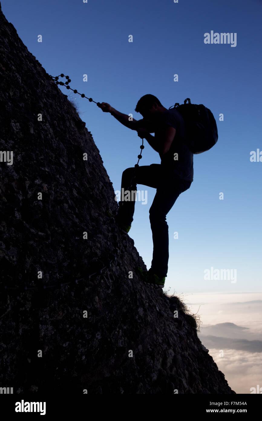 Man rappelling on the Arschbagge near summit of Mount Rigi, Bänderenweg route, Switzerland, Europe - Stock Image