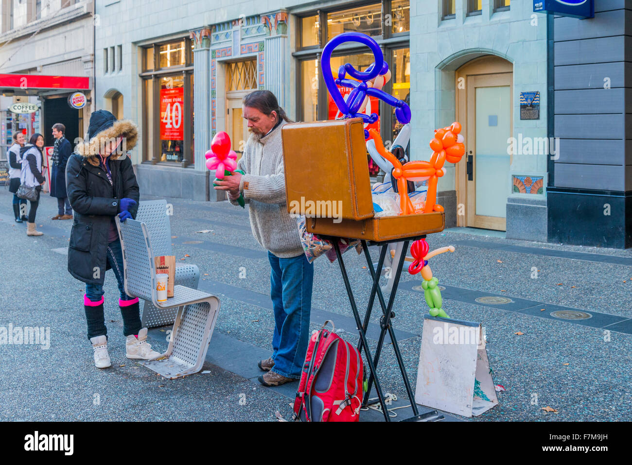 Balloon man makes flower for sad woman, Granville Street, Vancouver, British Columbia, Canada, - Stock Image