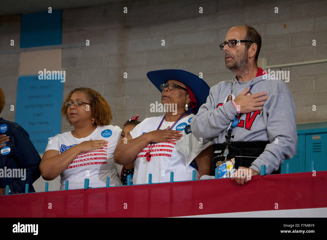 White man and black woman put hand on heart for pledge of allegiance at President Obama campaign rally at Orr Middle - Stock Image