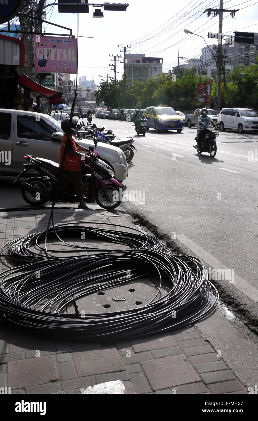Electrical cables coiled up on the sidewalk / pavement / roadside causing a dangerous obstruction in Pattaya Thailand - Stock Image