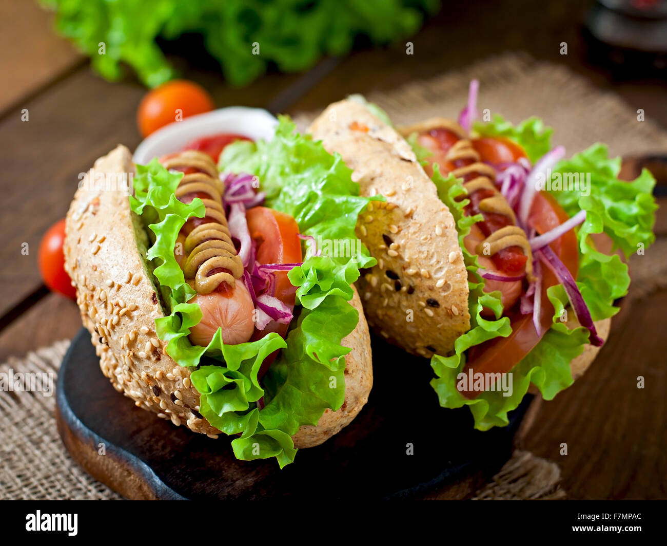 Hotdog with ketchup mustard and lettuce on wooden background - Stock Image