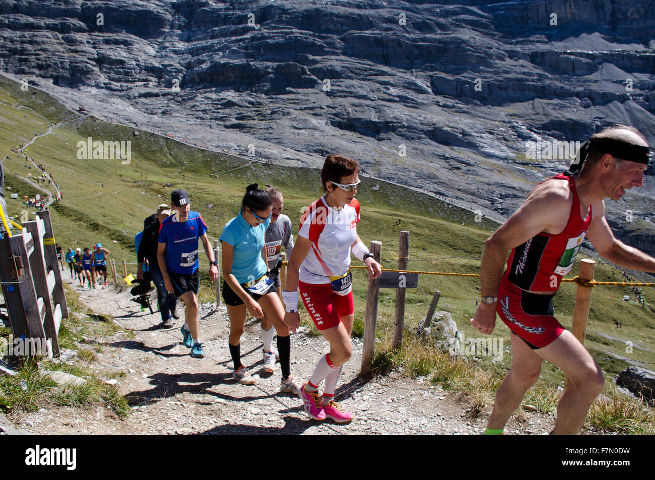 Runners on glacier moraine and last uphill stretch during 2015 Jungfrau Mountain Marathon race from Interlaken to - Stock Image
