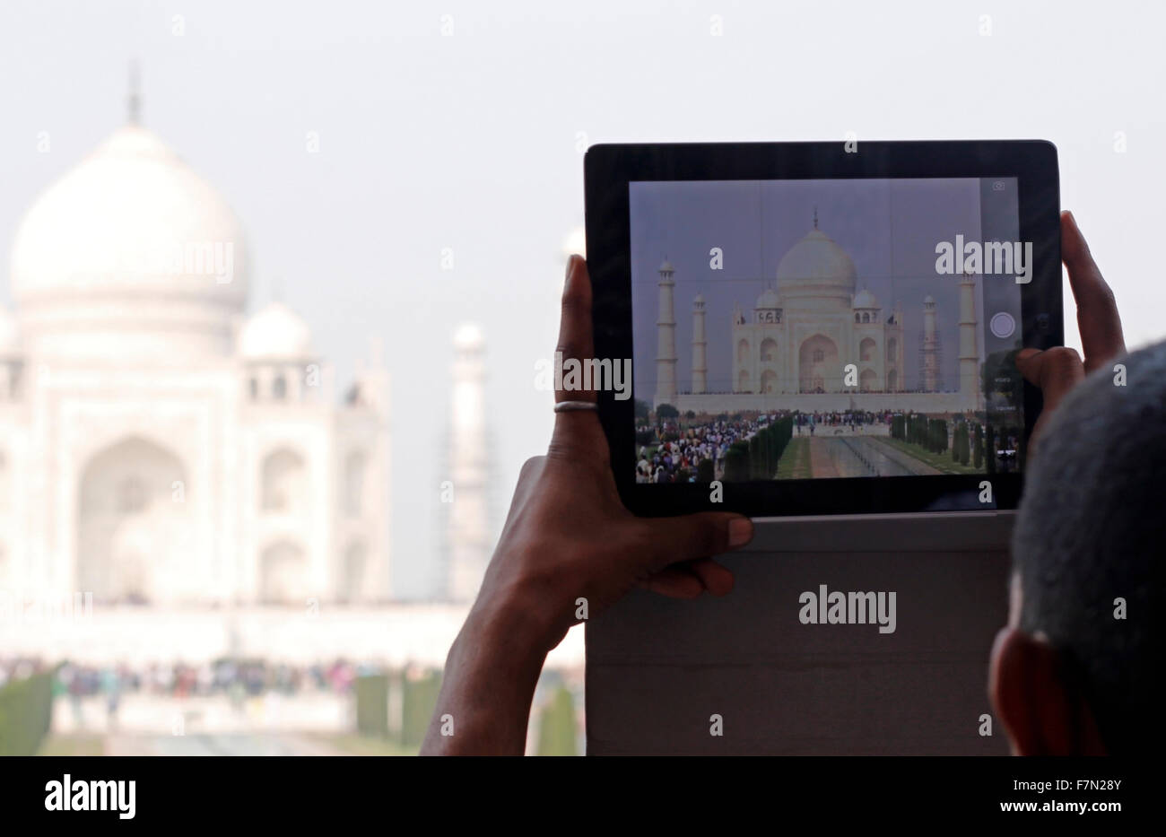 A Man Capturing Taj Mahal In his Tablet - Stock Image
