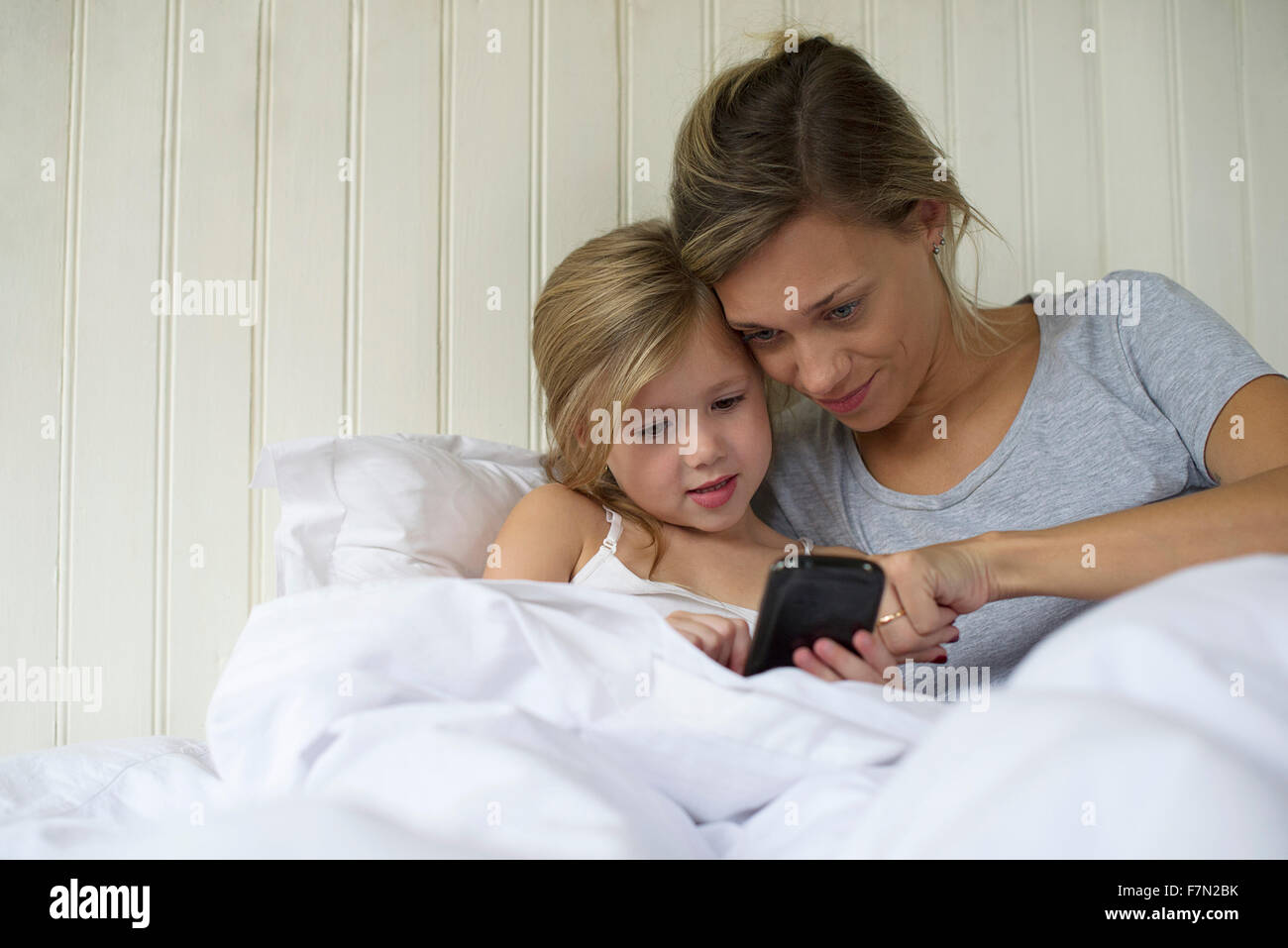 Mother and daughter using smartphone together - Stock Image