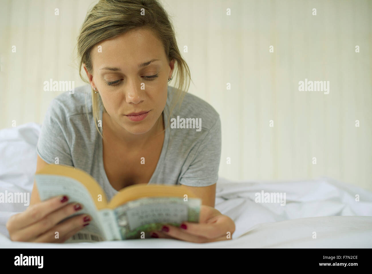 Woman lying on stomach reading book - Stock Image