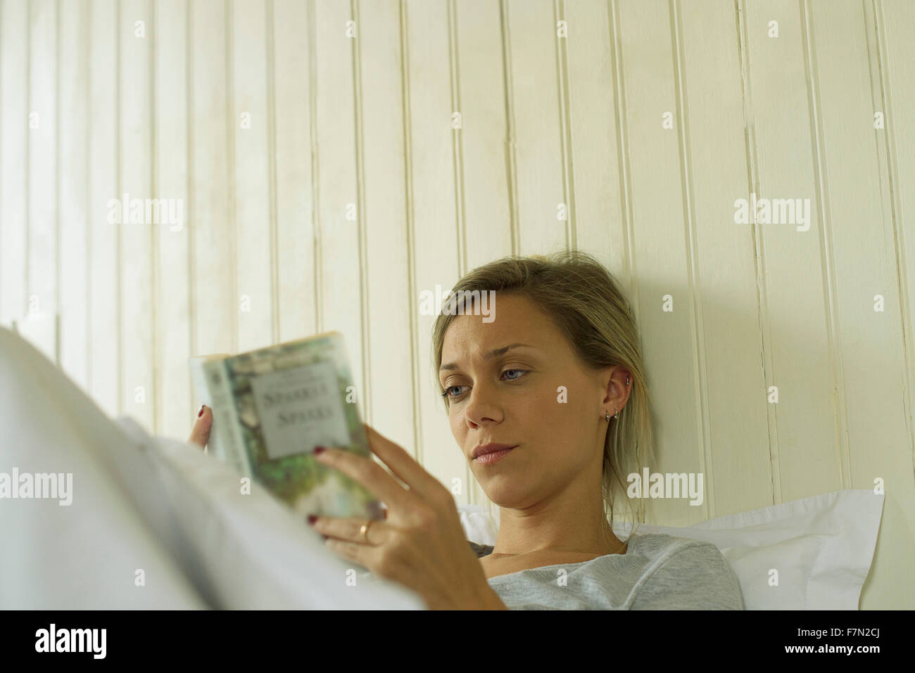 Woman reading in bed - Stock Image