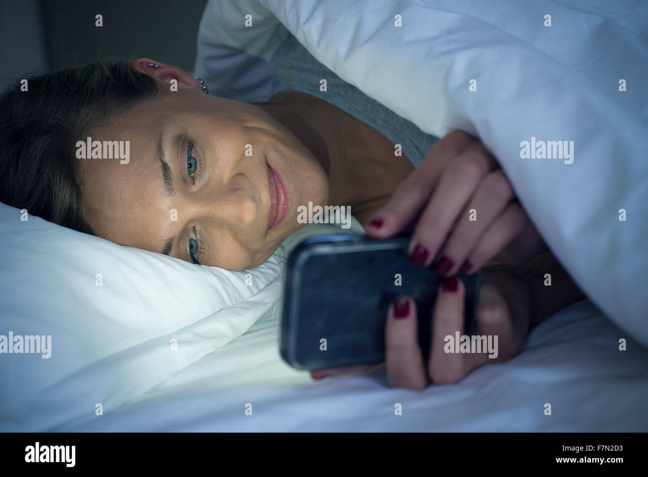 Woman lying in bed using smartphone Stock Photo