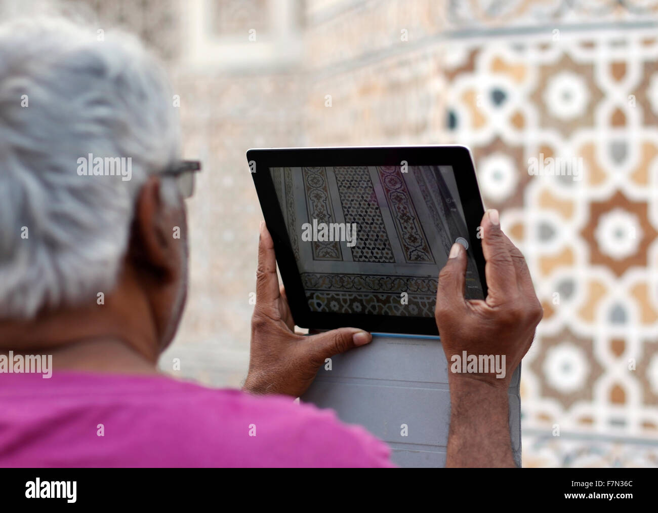 A old man Capturing India architecture through his tablet at Itmad-Ud-Daulah - Stock Image