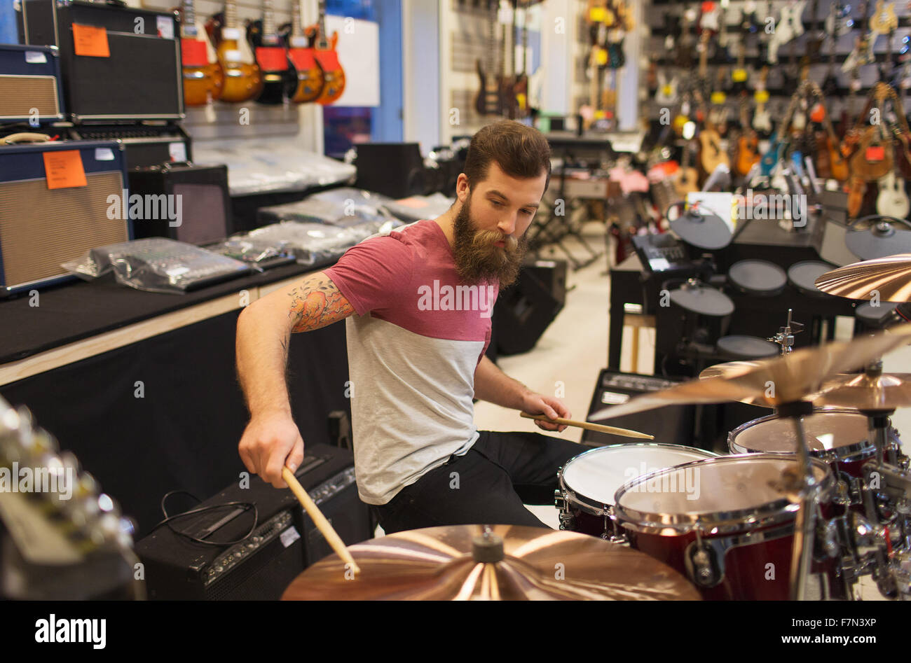 male musician playing cymbals at music store - Stock Image