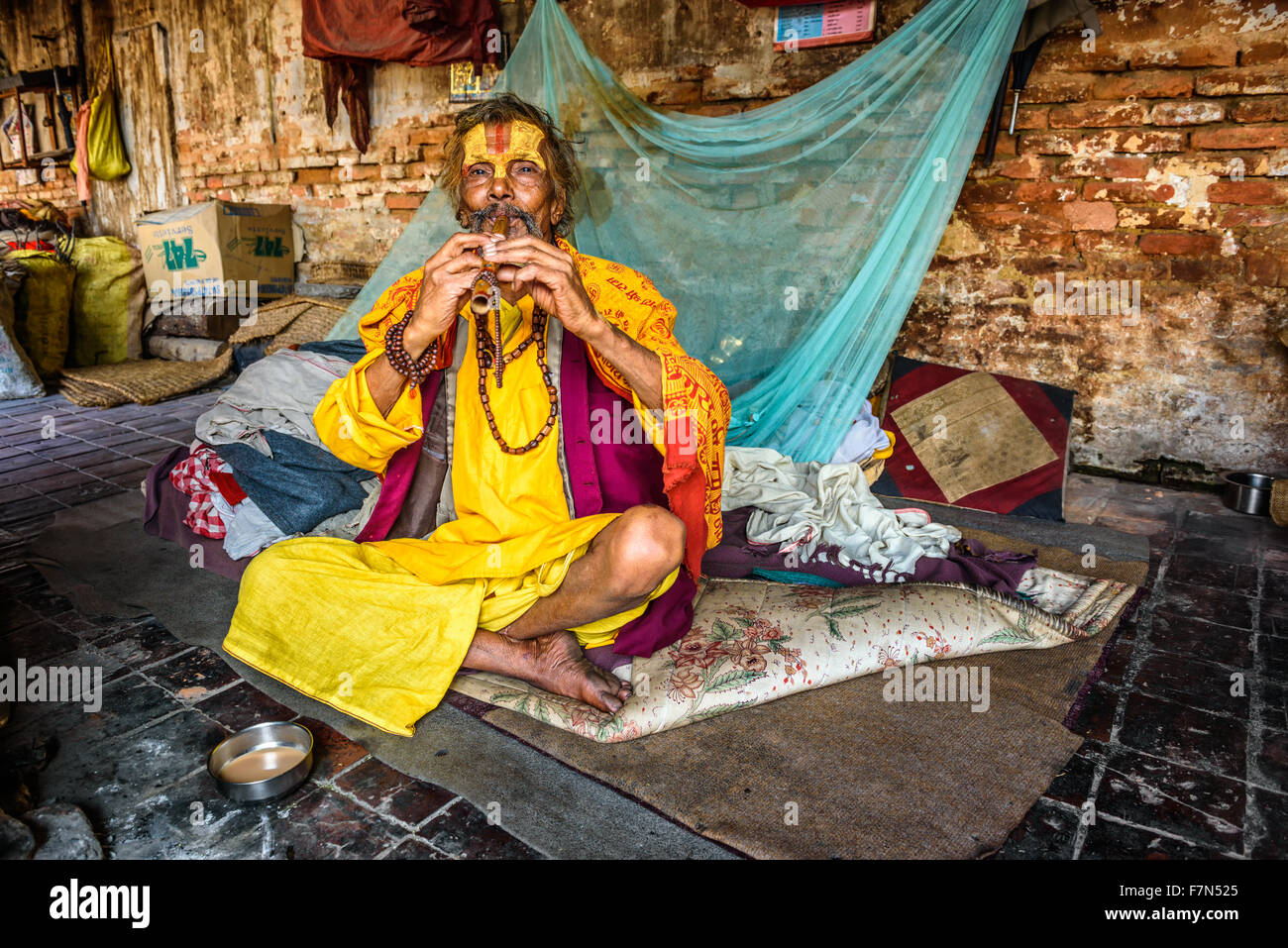 Sadhu baba (holy man) living in Pashupatinath Temple plays a pipe - Stock Image
