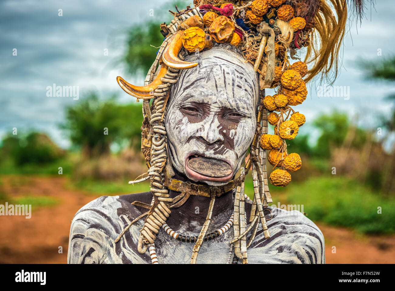 Old woman from the african tribe Mursi with lip plate in her village. - Stock Image