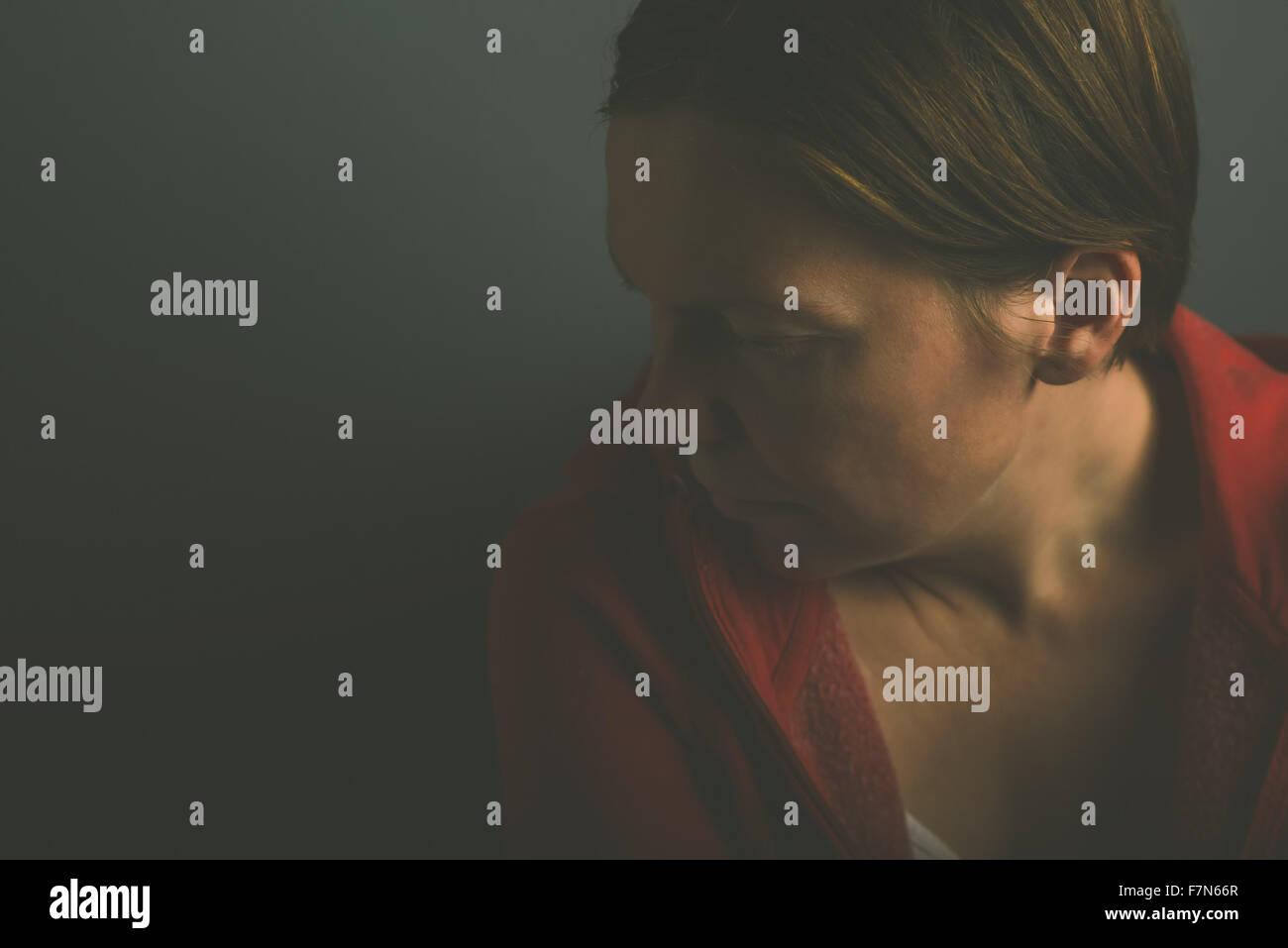 Depressive pessimistic lonely woman in dark room, low key portrait of sad adult female - Stock Image