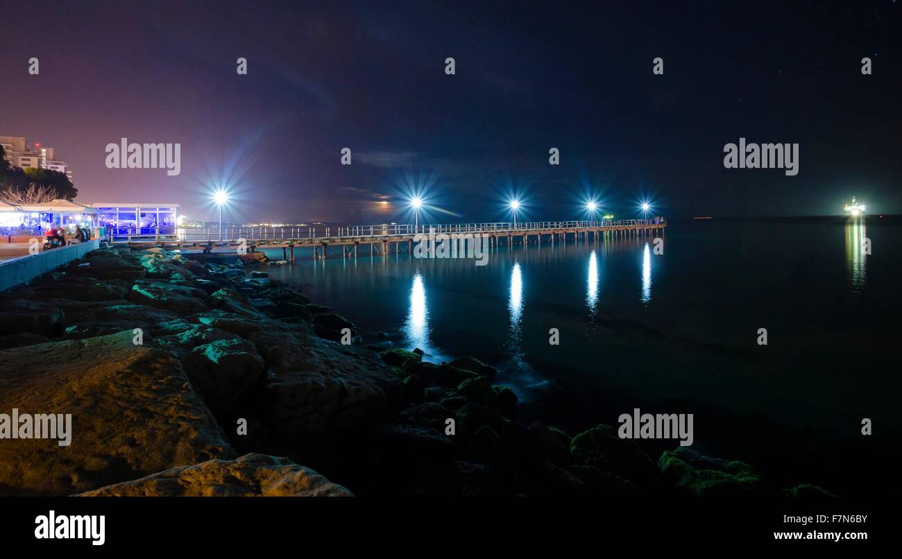 The Limassol pier in Enaerios Area in Cyprus. A night view of the city lights and the moon rising from the sea reflected - Stock Image