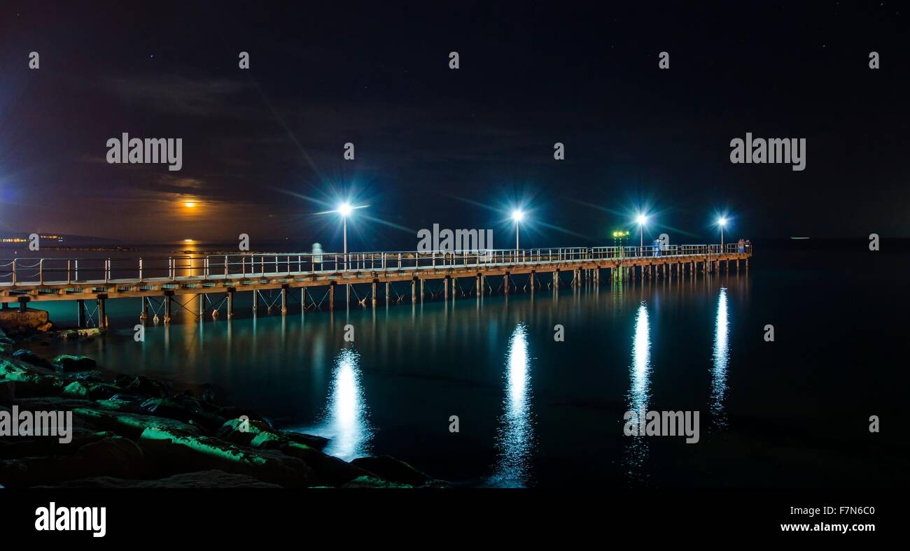 The Limassol pier in Enaerios Area in Cyprus. A night view of the city lights aligning to the moon as it rises from - Stock Image