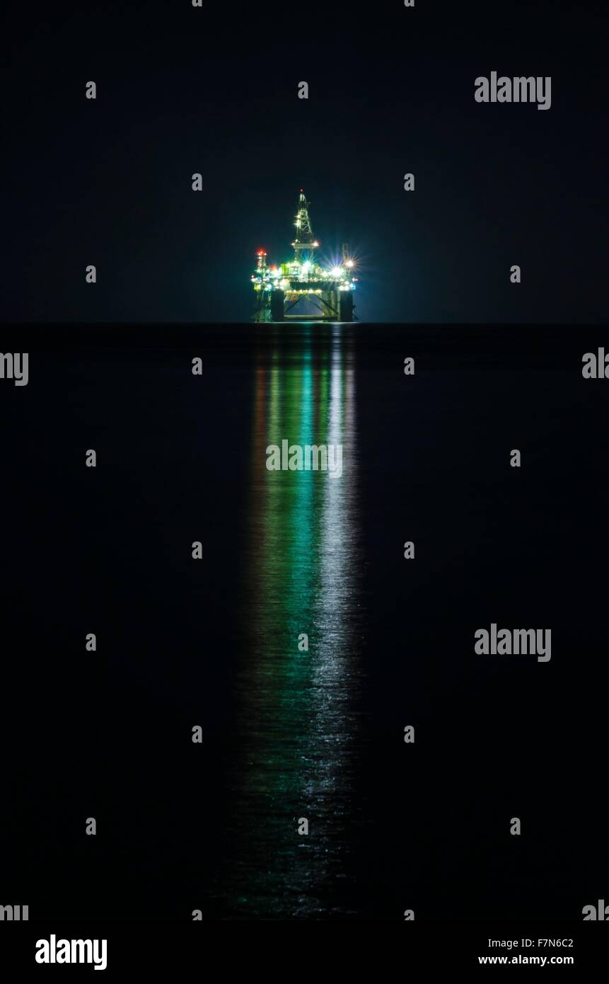 A night view of the oil drilling platform lit up on the coast of Limassol, in Cyprus. The oil rig is floating in - Stock Image