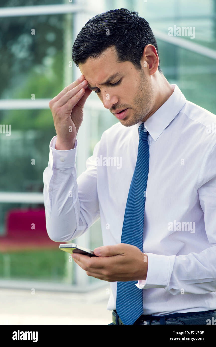 Businessman looking at cell phone with worried expression - Stock Image