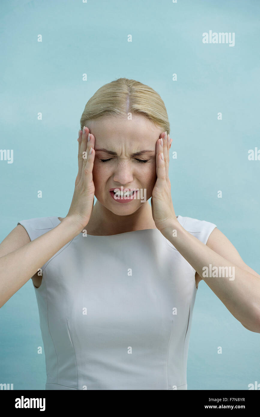 Woman holding head in frustration - Stock Image
